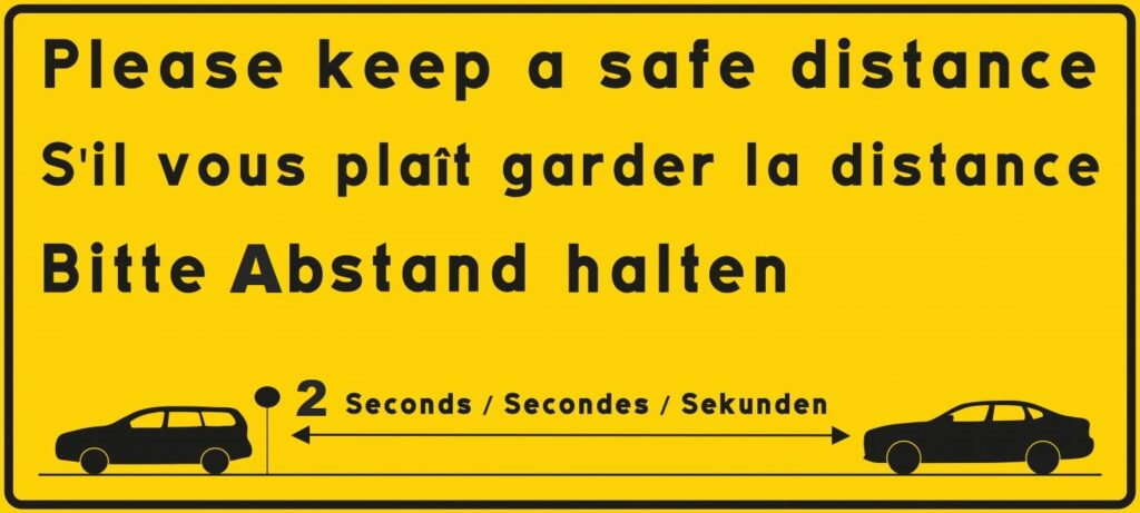 A safe distance sign in three languages which illustrates the two-second rule for vehicles